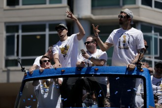 Klay Thompson, left, and Zaza Pachulia, right, ride on top of a double-decker bus during the Golden State Warriors' championship parade in Oakland, Calif., on Tuesday, June 12, 2018. The Warriors recently swept the Cleveland Cavaliers in the NBA Finals to win their third championship in four years. (Randy Vazquez/ Bay Area News Group)