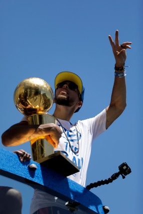 Stephen Curry waves at some fans during the Golden State Warriors' championship parade in Oakland, Calif., on Tuesday, June 12, 2018. The Warriors recently swept the Cleveland Cavaliers in the NBA Finals to win their third championship in four years. (Randy Vazquez/ Bay Area News Group)