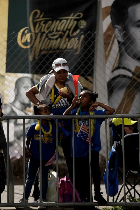 Madison Paysinger, 6, right, plays a horn, while Donna Banks, center, eats an apple, and her sister Gabrielle, 4, tries to play the horn also before the Golden State Warriors' championship parade in Oakland, Calif., on Tuesday, June 12, 2018. The Warriors recently swept the Cleveland Cavaliers in the NBA Finals to win their third championship in four years. (Randy Vazquez/ Bay Area News Group)