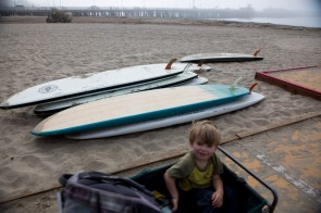 Ashton Keene, 3, is pulled in a cart passed some surf boards by his mother Caralyn at Cowell's Beach in Santa Cruz, Calif., on Thursday, June 21, 2018. A bill to make surfing the official sport of California is finding little resistance as it heads for a state Senate hearing. (Randy Vazquez/ Bay Area News Group)