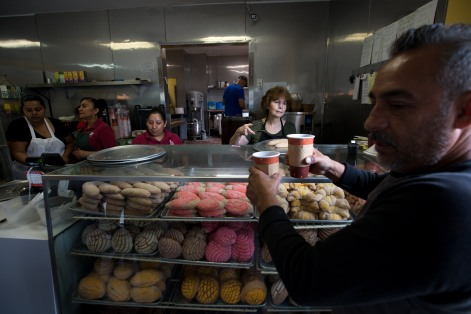 Miguel Zamora, right, gets his coffee from owner of Rico Pan Bakery Bertha Fernandez, center, on Calle Willow in San Jose, Calif., on Tuesday, Aug. 14, 2018. Calle Willow is a cultural hub for the Mexican community and its something Fernandez hopes is not pushed out by big business. (Randy Vazquez/ Bay Area News Group)