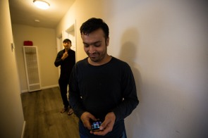 Muhammad Shakeel Naqvi, right, checks his phone while Shaid Muhammad, center, buttons his shirt in the hallway of their home in Menlo Park, Calif., on Tuesday, July 17, 2018. The two men rent rooms at a home owned by their employer Zareen Khan, owner of Zareen's Restaurant. Khan offers below-market rent to four of her key, full time employees. It's a unique way for a small business to keep its employees. (Randy Vazquez/ Bay Area News Group)