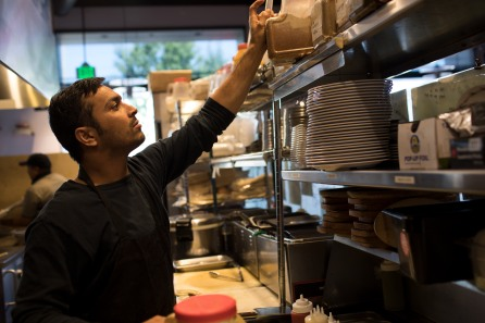 Muhammad Shakeel Naqvi grabs some spices at Zareen's Restaurant in Palo Alto, Calif., on Tuesday, July 17, 2018. Naqvi rents a room in a home owned by Zareen Khan, owner of Zareen's Restaurant. Khan offers below-market rent to four of her key, full time employees. It's a unique way for a small business to keep its employees. (Randy Vazquez/ Bay Area News Group)