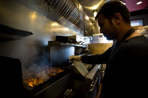 Muhammad Shakeel Naqvi cooks some chicken at Zareen's Restaurant in Palo Alto, Calif., on Tuesday, July 17, 2018. Naqvi rents a room in a home owned by Zareen Khan, owner of Zareen's Restaurant. Khan offers below-market rent to four of her key, full time employees. It's a unique way for a small business to keep its employees. (Randy Vazquez/ Bay Area News Group)
