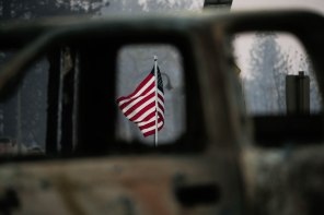 An American flag is photographed through the window of a car that was burned during the Camp Fire in Paradise, Calif., on Sunday, Nov. 11, 2018. (Randy Vazquez/Bay Area News Group)