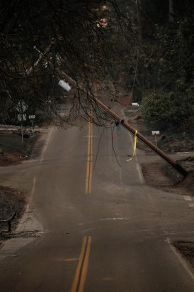 A power line pole hangs over Pearson Road in Paradise, Calif., on Sunday, Nov. 11, 2018. (Randy Vazquez/Bay Area News Group)