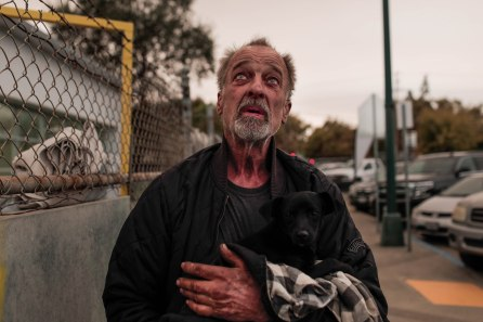 Daniel Woida holds a dog he rescued outside of a shelter at the Butte County Fairgrounds in Gridley, Calif., on Friday, Nov. 9, 2018. Many evacuees of the deadly Camp Fire came to the shelter. (Randy Vazquez/Bay Area News Group)
