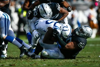 Oakland Raiders' Johnathan Hankins (90), right, tackles Indianapolis Colts' Marlon Mack (25), center, in the third quarter of their NFL game at the Coliseum in Oakland, Calif., on Sunday, Oct. 28, 2018. (Randy Vazquez/Bay Area News Group)
