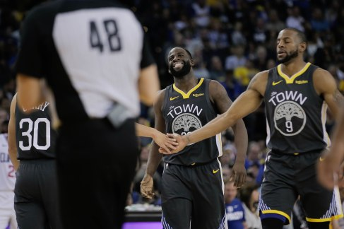 Golden State Warriors' Draymond Green (23), center, grimaces in pain after getting fouled by a Los Angeles Clippers defender during the second quarter of their game at Oracle Arena in Oakland, Calif., on Sunday, Dec. 23, 2018. (Randy Vazquez/Bay Area News Group)