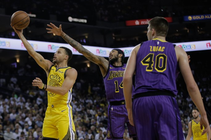 Golden State Warriors' Stephen Curry (30), left, scores a layup while being guarded by Los Angeles Lakers' Brandon Ingram (14), center, during the first quarter of their game at Oracle Arena in Oakland, Calif., on Tuesday, Dec. 25, 2018. (Randy Vazquez/Bay Area News Group)