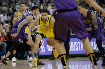 Golden State Warriors' Klay Thompson (11), center, dribbles through a pair of Los Angeles Lakers defenders during the first quarter of their game at Oracle Arena in Oakland, Calif., on Tuesday, Dec. 25, 2018. (Randy Vazquez/Bay Area News Group)
