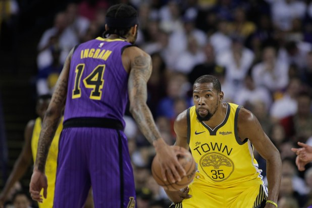 Golden State Warriors' Kevin Durant (35), right, sticks his tongue out while guarding Los Angeles Lakers' Brandon Ingram (14), left, during the first quarter of their game at Oracle Arena in Oakland, Calif., on Tuesday, Dec. 25, 2018. (Randy Vazquez/Bay Area News Group)