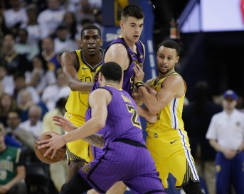 Golden State Warriors' Stephen Curry (30), right, and teammate Kevon Looney (5), left, try and get around a screen from Los Angeles Lakers' Ivica Zubac (40), center, as Lakers' Lonzo Ball (2) dribbles the basketball during the first quarter of their game at Oracle Arena in Oakland, Calif., on Tuesday, Dec. 25, 2018. (Randy Vazquez/Bay Area News Group)