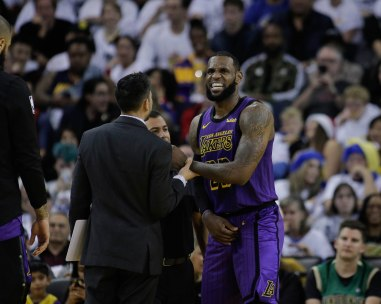 Los Angeles Lakers' LeBron James (23) looks to be in pain during the third quarter of their game versus the Golden State Warriors at Oracle Arena in Oakland, Calif., on Tuesday, Dec. 25, 2018. (Randy Vazquez/Bay Area News Group)