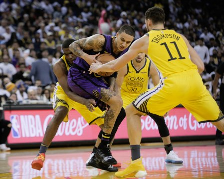 Los Angeles Lakers' Kyle Kuzma (0), center, tries to keep the ball away from Golden State Warriors defenders during the third quarter of their game at Oracle Arena in Oakland, Calif., on Tuesday, Dec. 25, 2018. (Randy Vazquez/Bay Area News Group)