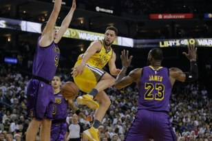 Golden State Warriors' Klay Thompson (11), center, makes a pass between Los Angeles Lakers' Ivica Zubac (40), left, and LeBron James (23), right, during the first quarter of their game at Oracle Arena in Oakland, Calif., on Tuesday, Dec. 25, 2018. (Randy Vazquez/Bay Area News Group)
