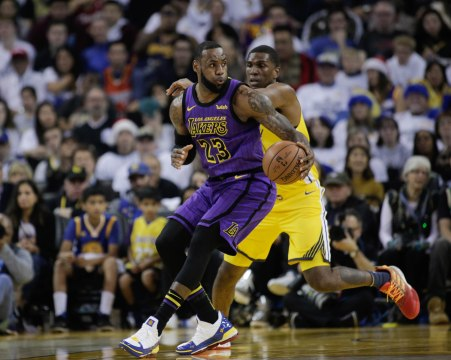 Los Angeles Lakers' LeBron James (23), left, is guarded by Golden State Warriors' Kevon Looney (5), right, during the first quarter of their game at Oracle Arena in Oakland, Calif., on Tuesday, Dec. 25, 2018. (Randy Vazquez/Bay Area News Group)