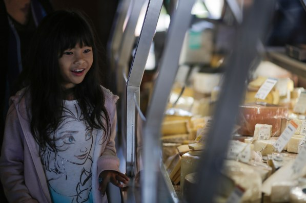 Lael Moreno, left, looks at the various cheeses behind the glass counter at The Cheese School of San Francisco on Thursday, Oct. 18, 2018. (Randy Vazquez/Bay Area News Group)