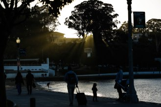 Light leaks through the trees as people walk along the water at San Francisco Maritime National Historical Park near Ghirardelli Square in San Francisco on Thursday, Oct. 18, 2018. (Randy Vazquez/Bay Area News Group)