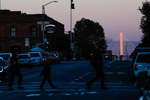The Bay Bridge is seen in the distance as people cross Beach Street to Ghirardelli Square in San Francisco on Thursday, Oct. 18, 2018. (Randy Vazquez/Bay Area News Group)