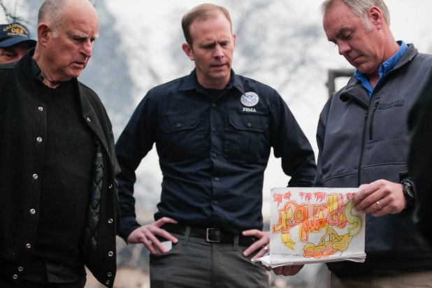 Governor of California Jerry Brown, left, FEMA administrator Brock Long, center, watch U.S. Secretary of the Interior Ryan Zinke, right, go through school work that was recovered from Paradise Elementary in Paradise, Calif., on Wednesday, Nov. 14, 2018. (Randy Vazquez/Bay Area News Group)