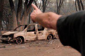 Brad Weldon points at a burned car in his neighborhood in Paradise, Calif., on Monday, Nov. 12, 2018. Weldon and friend Michiel McCrary chose not to evacuate during the Camp Fire and fought off flames and kept Brad's home and his 90-year-old mother safe. (Randy Vazquez/Bay Area News Group)