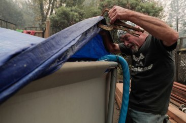 Brad Weldon lifts the tarp from his pool behind his home in Paradise, Calif., on Monday, Nov. 12, 2018. Brad and friend Michiel McCrary used water from the pool to fight the flames from the Camp Fire and kept Brad's home and his 90-year-old mother safe. (Randy Vazquez/Bay Area News Group)