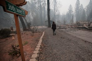 "Mayor Jody Jones walks down to her home in Paradise, Calif., on Wednesday, Nov. 14, 2018. Her house was burned during the Camp Fire last week. A sign that reads ""Jody Jones Way"" still stands in front of her property. (Randy Vazquez/Bay Area News Group)"