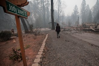 """Mayor Jody Jones walks down to her home in Paradise, Calif., on Wednesday, Nov. 14, 2018. Her house was burned during the Camp Fire last week. A sign that reads """"Jody Jones Way"""" still stands in front of her property. (Randy Vazquez/Bay Area News Group)"""