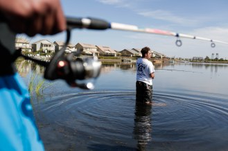 Cameron Perkins, right, fishes in a lake in the River Island community in Lathrop, Calif., on Sunday, Sep. 30, 2018. (Randy Vazquez/Bay Area News Group)