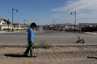 Haramrit Sohal, 6, walks on a dirt road on the outskirts of the River Island community in Lathrop, Calif., on Sunday, Sep. 30, 2018. (Randy Vazquez/Bay Area News Group)