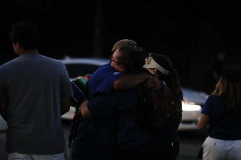 People hug each other at a reunification center at Gavilan College in Gilroy, Calif., on Sunday, July 28, 2019. People were directed to the center following a shooting at the Gilroy Garlic Festival. (Randy Vazquez/Bay Area News Group)