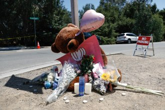 People place candles, flowers and a teddy bear outside of Christmas Hill Park in Gilroy, Calif., on Monday, July 30, 2019. The park was the location of the Gilroy Garlic Festival where a gunman opened fire resulting in three deaths. The gunman was also killed. (Randy Vazquez/Bay Area News Group)