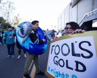 "John Tello, left, carries an inflatable shark while Monica Rodrigues, right, hold a sign that says ""Fool's Gold"" outside of SAP Center in San Jose, Calif., on Tuesday, April 23, 2019. (Randy Vazquez/Bay Area News Group)"