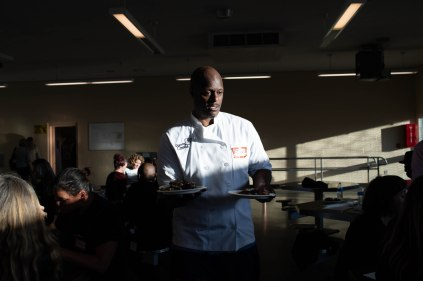 Phillip Sims, a student in the Quentin Cooks program, serves food to guest during graduation dinner at San Quentin State Prison in San Quentin, Calif., on Wednesday, May 22, 2019. The all-volunteer program, brings chefs and inmates together to teach inmates how to work in a commercial kitchen. (Randy Vazquez/Bay Area News Group)