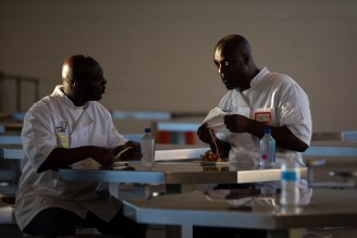 Ron Simmons, left, and Phillip Sims, right, eat some of the food they cooked during the graduation dinner of the Quentin Cooks program at San Quentin State Prison in San Quentin, Calif., on Wednesday, May 22, 2019. The all-volunteer program, brings chefs and inmates together to teach inmates how to work in a commercial kitchen. (Randy Vazquez/Bay Area News Group)