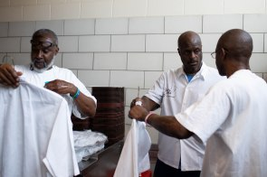 Alvis Tayor, left, Phillip Sims, center, and Freddie Grigsby, right, get their chef robes ready before graduation dinner of the Quentin Cooks program at San Quentin State Prison in San Quentin, Calif., on Wednesday, May 22, 2019. The all-volunteer program, brings chefs and inmates together to teach inmates how to work in a commercial kitchen. (Randy Vazquez/Bay Area News Group)