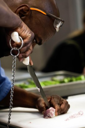 """Derry """"Brother D"""" Brown slices an onion during a class of the Quentin Cooks program at San Quentin State Prison in San Quentin, Calif., on Wednesday, May 15, 2019. The all-volunteer program, brings chefs and inmates together to teach inmates how to work in a commercial kitchen. (Randy Vazquez/Bay Area News Group)"""
