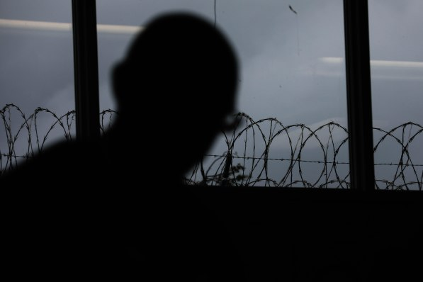 Barbed wire is seen through a window behind the silhouette of Kerry Rudd during a class of the Quentin Cooks program at San Quentin State Prison in San Quentin, Calif., on Wednesday, May 15, 2019. The all-volunteer program, brings chefs and inmates together to teach inmates how to work in a commercial kitchen. (Randy Vazquez/Bay Area News Group)