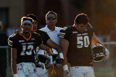 Saint Francis head coach Greg Calcagno, center, comes out wit his players Mose Vavao (50), right, and Travis Bell-Dzide (13), left, before their game versus Corona del Mar at Saint Francis High School in Mountain View, Calif., on Friday, Aug. 30, 2019. (Randy Vazquez/Bay Area News Group)