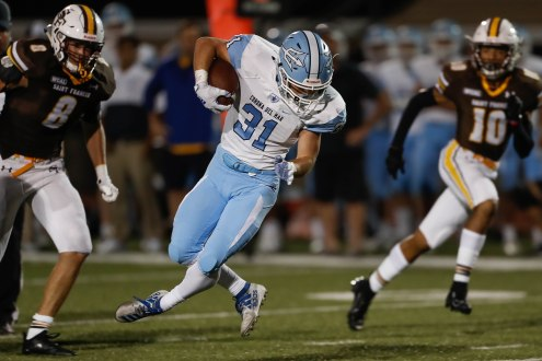 Corona del Mar's Riley Binnequist (31), center, runs through a pair of Saint Francis defenders during the third quarter of their game at Saint Francis High School in Mountain View, Calif., on Friday, Aug. 30, 2019. (Randy Vazquez/Bay Area News Group)