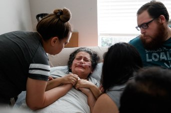 SAN JOSE - MAY 5: Claudia Meza, center, holds the hands of her family members after finding out her sister Mercedes Hartwig and brother-in-law Richard died at her home in San Jose, Calif., on Tuesday, May 5, 2020. Meza, who spent 48 days in the hospital sick with coronavirus, was told that while she was sedated with a breathing tube, her sister and brother-in-law died of the same virus. (Randy Vazquez / Bay Area News Group)