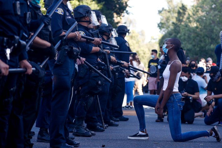 SAN JOSE - MAY 29: A protester kneels in front of officers as police try to push protesters back on East Santa Clara Street during a protest decrying the police killing of George Floyd in downtown San Jose on Friday, May 29, 2020. (Randy Vazquez / Bay Area News Group)